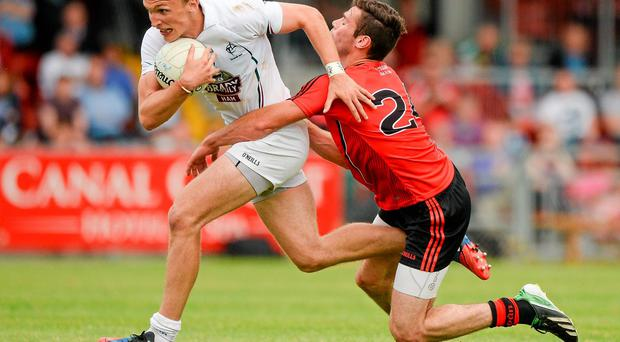 Kildare's Tommy Moolick breaks through a tackle by Conor Toner of Down during their qualifier clash at Páirc Esler. Photo: Piaras O Midheach / SPORTSFILE