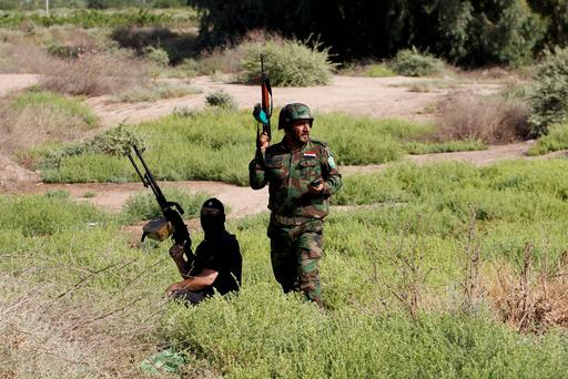 Armed Shi'ite volunteers from brigades loyal to radical cleric Muqtada al-Sadr, take their positions during a military advance in areas under the control of militants of the Islamic State, formerly known as the Islamic State in Iraq and the Levant (ISIL), on the outskirts of Samarra. Reuters