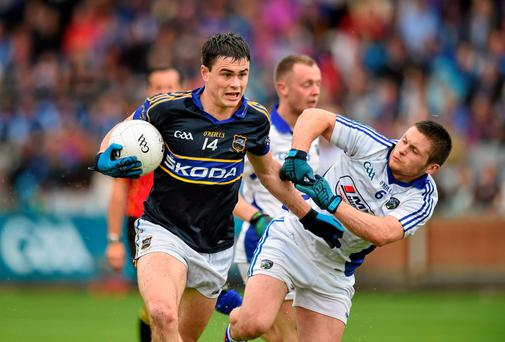 Man of the match Michael Quinlivan of Tipperary brushes off a challenge from Laois's Robbie Kehoe in his side's qualifier win at O'Moore Park. Photo: Matt Browne / SPORTSFILE