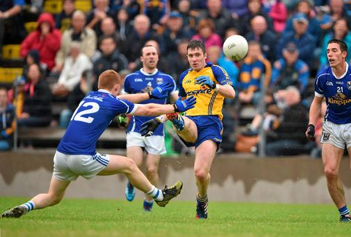 Roscommon's Cathal Cregg kicks a point despite the best efforts of Niall McDermott of Cavan during their qualifier clash at Kingspan Breffni Park. Photo: Brendan Moran / SPORTSFILE
