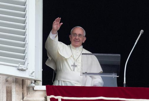 Pope Francis waves as he arrives for the Angelus prayer he delivers from the studio window overlooking St. Peter square at the Vatican yesterday.