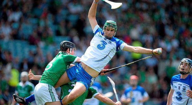 Waterford's Cormac Curran catches the sliotar ahead of LImerick duo Paddy O'Loughlin and Sean Finn during the Munster MHC final at Pairc Uí Chaoimh. Photo: Brendan Moran / SPORTSFILE