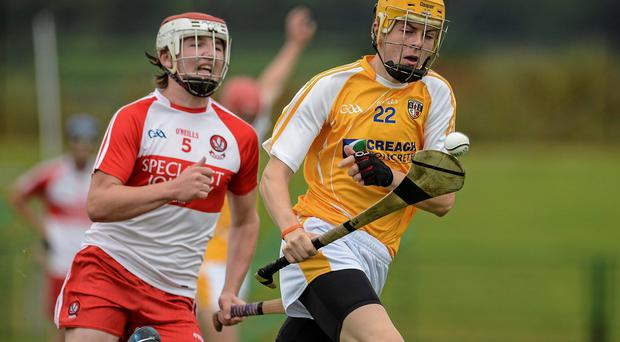 Antrim's Caolan McCaughan races clear of Gabriel Farren of Derry during the Ulster minor hurling championship final at Owenbeg. Photo: Oliver McVeigh / SPORTSFILE