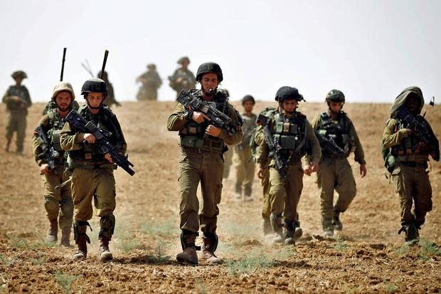 Israeli soldiers from the Nahal Infantry Brigade walk across a field near central Gaza Strip. Reuters