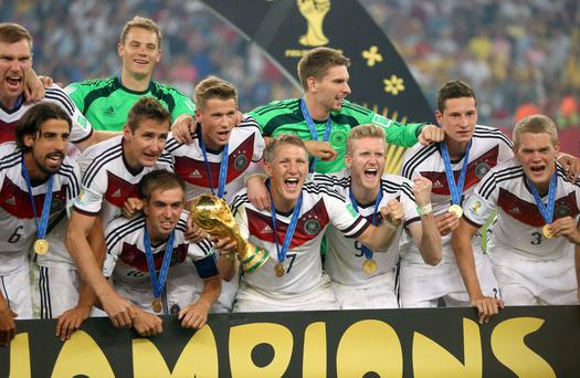 Bastian Schweinsteiger, holding the trophy, celebrates with his team-mates after Germany defeated Argentina 1-0 in the World Cup final