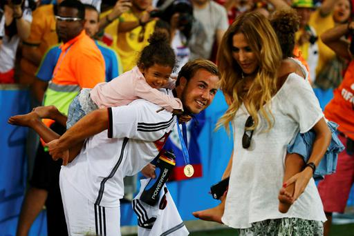 Germany's Mario Goetze and his girlfriend Kathrin Brommel (R) carry the twin daughters of teammate Jerome Boateng, Soley and Lamia, at the end of during their 2014 World Cup final against Argentina at the Maracana stadium in Rio de Janeiro July 13, 2014. REUTERS/Kai Pfaffenbach (BRAZIL - Tags: SPORT SOCCER WORLD CUP ENTERTAINMENT TPX IMAGES OF THE DAY)
