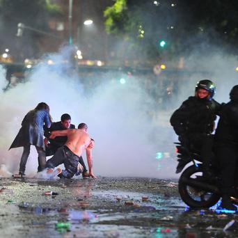 Soccer fans try to escape from a tear gas cloud and a police water cannon, used to restrain a group of youths who hurled rocks and vandalized stores, at a rally after Argentina's performance in a 1-0 loss to Germany in the World Cup finals. Photo: Reuters