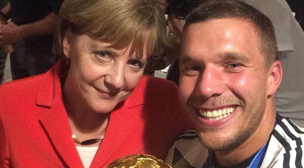 Lukas Podolski and Angela Merkel pose with the World Cup trophy