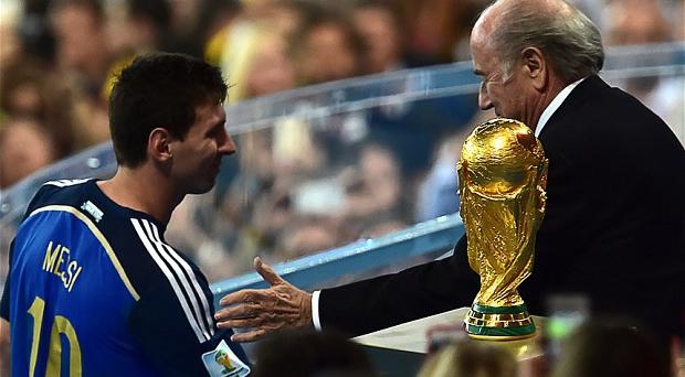 FIFA President Joseph Blatter congratulates Argentina's forward and captain Lionel Messi after he won the golden balls award after the 2014 FIFA World Cup final football match between Germany and Argentina at the Maracana Stadium in Rio de Janeiro on July 13, 2014. AFP PHOTO / NELSON ALMEIDANELSON ALMEIDA/AFP/Getty Images