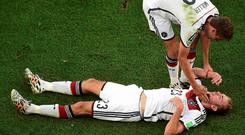 Germany's Thomas Mueller helps up teammate Christoph Kramer after his heavy collision in the World Cup final against Argentina at the Maracana stadium