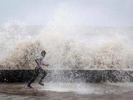 A school boy runs to get drenched in a large wave during high tide at a sea front in Mumbai. Weak rainfall in India since the start June, when the monsoon season began, has raised concerns of a first drought in five years, although weather experts are hopeful rains will revive in the next week. Photo credit: REUTERS/Danish Siddiqui