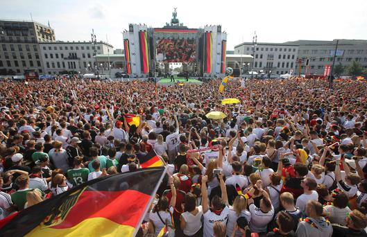 German soccer fans cheer as they wait for the arrival of their team, winners of the 2014 World Cup, near the Brandenburg Gate in Berlin, July 15, 2014