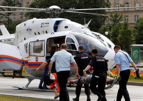 Members of the emergency services carry an injured passenger outside a metro station following an accident on the subway in Moscow July 15, 2014