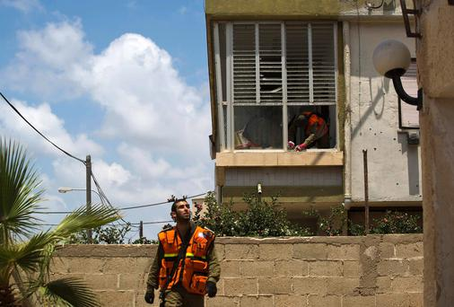 An Israeli soldier clears debris at the scene after a rocket fired by Palestinian militants in Gaza landed in Ashdod July 15, 2014
