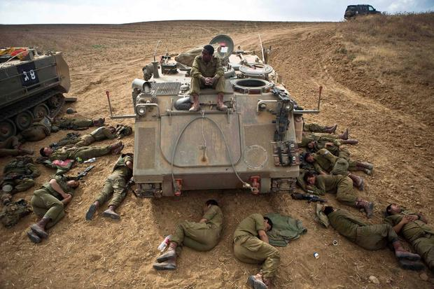 Israeli soldiers sleep on the ground next to an armoured personnel carrier (APC) outside the Gaza Strip July 15, 2014
