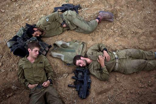 Israeli soldiers sleep on the ground next to their weapons outside the Gaza Strip July 15, 2014
