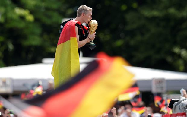 Bastian Schweinsteiger kisses the trophy during a fan party after the arrival of the German national soccer team in Berlin Tuesday, July 15, 2014. Germany beat Argentina 1-0 on Sunday to win its fourth World Cup title. (AP Photo/Petr David Josek)