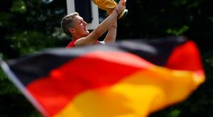 Bastian Schweinsteiger lifts up the World Cup trophy on a stage during celebrations to mark the team's 2014 Brazil World Cup victory, at a 'fan mile' public viewing zone in Berlin