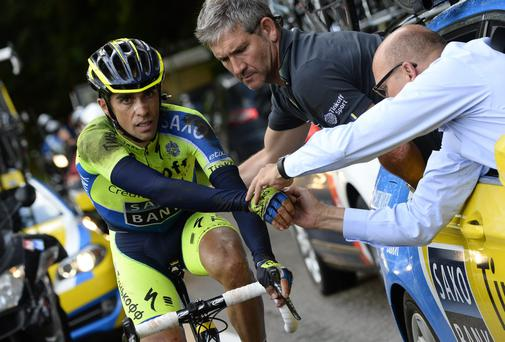 Tinkoff-Saxo team manager Bjarne Riis helps Spain's Alberto Contador as he rides on after a fall which eventually ended his Tour de France on stage ten of the race. Photo:LIONEL BONAVENTURE/AFP/Getty Images
