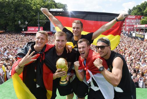 Germany's Bastian Schweinsteiger, Per Mertesacker, Manuel Neuer, Kevin Grosskreutz and Lukas Podolski pose with the World Cup trophy in Berlin. Photo: Markus Gilliar - Pool /Getty Images