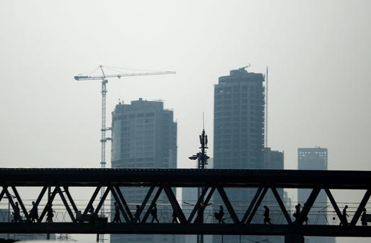 Pedestrians walk on an overhead bridge at a subway station in front of buildings under construction, in Beijing, July 15, 2014. China's leaders are expecting to see a dividend from three months of stimulus spending in second-quarter growth data on July 16, 2014, but the economy may need even more state support to meet this year's growth target of 7.5 percent