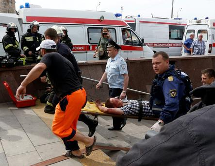 ATTENTION EDITORS - VISUAL COVERAGE OF SCENES OF INJURY OR DEATH Members of the emergency services carry an injured passenger outside a metro station following an accident on the subway in Moscow July 15, 2014. Nineteen people were killed on Tuesday and up to 120 injured when a Moscow underground train derailed between two stations during the morning rush hour, the Emergencies Ministry said. REUTERS/Sergei Karpukhin (RUSSIA - Tags: DISASTER TRANSPORT TPX IMAGES OF THE DAY)