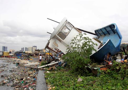 People walk among debris and a boat destroyed by strong winds brought by Typhoon Rammasun that battered coastal bay of Baseco compound, metro Manila