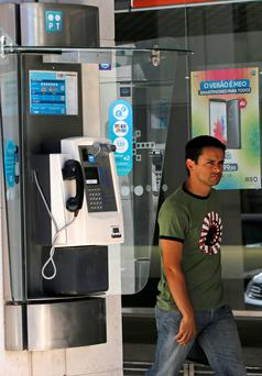 A man walks past a Portugal Telecom public phone in Lisbon July 13, 2014