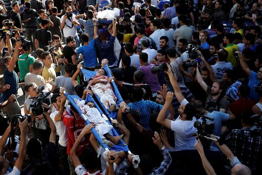 The bodies of three of the four Palestinian children from the Baker family, whom medics said were killed by a shell fired by an Israeli naval gunboat, is carried from the morgue in Gaza City.Photo: REUTERS/Finbarr O'Reilly