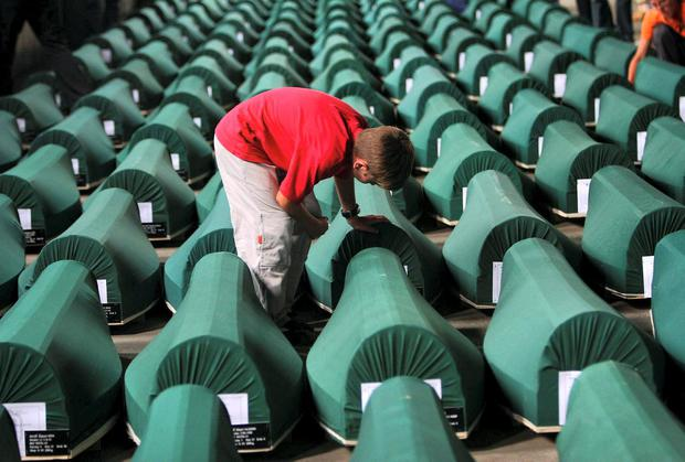 A boy reads the names on coffins which contain the bodies of Bosnian Muslims. The bodies were found in a mass grave near Srebrenica, Bosnia in 2005. They had been killed near the end of the war by Bosnian Serbs. Photo credit: AP Photo/Dusan Vranic