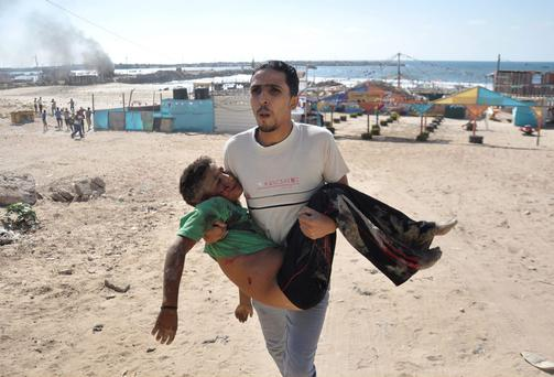 A Palestinian man carries the body of a boy, who medics said was killed by a shell on a beach in Gaza City. Photo credit: REUTERS/Mohammed Talatene