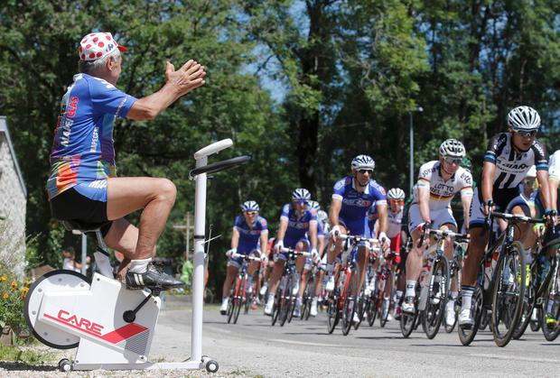 A cycling fan on a home trainer cheers as the pack of riders cycles on its way during the 187.5km 11th stage of the Tour de France between Besancon and Oyonnax. Photo: REUTERS/Christian Hartmann