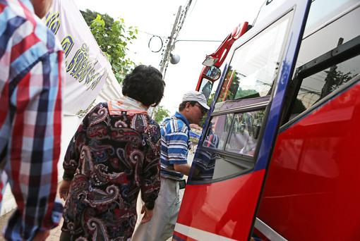 CHIANG MAI, THAILAND - APRIL 17: Chinese tourists board a bus after visiting temples on April 17, 2014 in Chiang Mai, Thailand. Due to a rapidly growing economy, more than 100 million mainland Chinese are expected to go abroad this year. In Chiang Mai, which is seeing a surge in Chinese tourism after a popular Chinese movie was set there with a recent poll finding that 80% of residents were displeased with Chinese behavior while abroad. (Photo by Taylor Weidman/Getty Images)