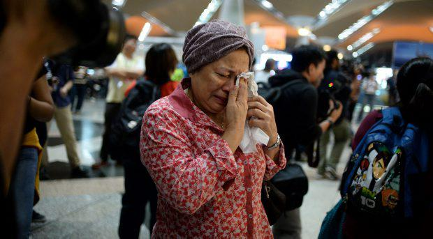 A woman reacts to news regarding a Malaysia MH17 at Kuala Lumpur International Airport in Sepang