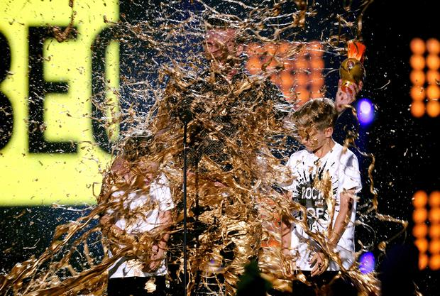Soccer player David Beckham (C) with Cruz Beckham (L) and Romeo Beckham (R) get slimed onstage during Nickelodeon Kids' Choice Sports Awards 2014