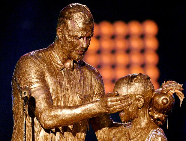 Soccer player David Beckham (L) and Romeo Beckham get slimed onstage during Nickelodeon Kids' Choice Sports Awards 2014