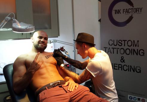 Irish cage fighter Cathal Pendred gets a semi-permanent UFC logo stamp on his chest at The Ink Factory tattoo parlour ahead of his UFC debut this Saturday