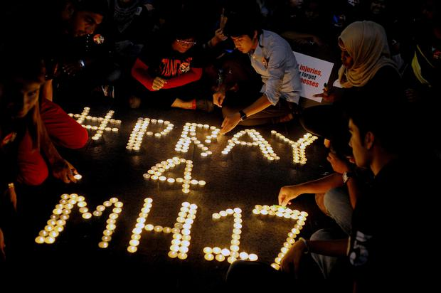 People arrange candles to offer prayers for the victims of the Malaysia Airlines Flight 17, at a shopping mall in Petaling Jaya, near Kuala Lumpur, Malaysia, Friday, July 18, 2014. The Malaysia Airlines jetliner was carrying 298 people when it was shot down over eastern Ukraine on Thursday in eastern Ukraine, sending shockwaves around the world from Malaysia to the Netherlands. (AP Photo/Joshua Paul)