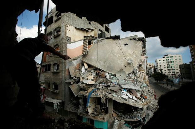 A man looks at a destroyed house, which police said was targeted on Friday in an Israeli air strike, through a hole, in Gaza City July 19, 2014