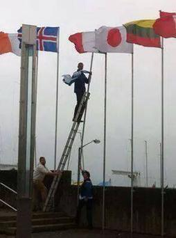 Cllr Hugh Lewis taking down the Israeli flag in Dublin.