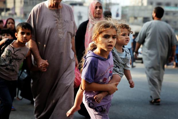 Palestinians flee the Shujayeh neighbourhood during heavy Israeli shelling in Gaza City July 20, 2014.