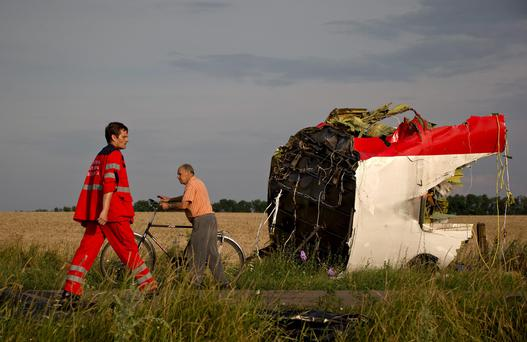 A paramedic walks by a part of fuselage at the crash site of Malaysia Airlines Flight 17 near the village of Hrabove, eastern Ukraine
