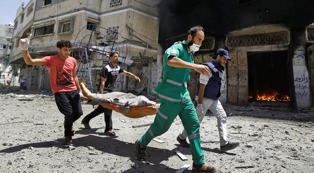 Palestinian medics carry a casualty as they run past a burning building in Gaza City's Shijaiyah neighborhood, northern Gaza Strip, Sunday