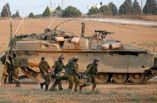 Israeli soldiers carry a comrade on a stretcher, who was wounded during an offensive in Gaza