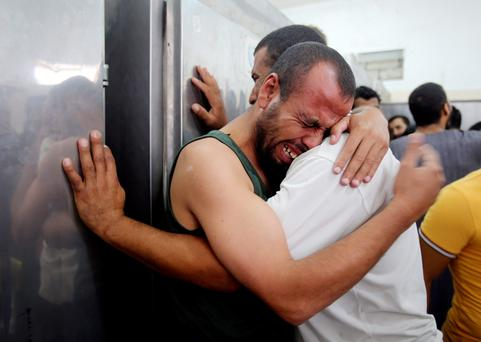 Palestinians mourn the death of their relatives, whom medics said were killed in Israeli shelling, at a hospital morgue in Rafah in the southern Gaza Strip