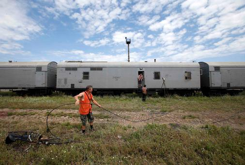 Railway employees are pictured as they work near refrigerator wagons, which according to employees and local residents contain bodies of passengers of the crashed Malaysia Airlines Boeing 777 plane, at a railway station in the town of Torez, Donetsk region July 20, 2014