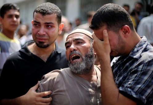 The father (C) of Palestinian man Zakareya al-Ashqar, who medics said was killed during heavy Israeli shelling, reacts outside a hospital morgue in Gaza City