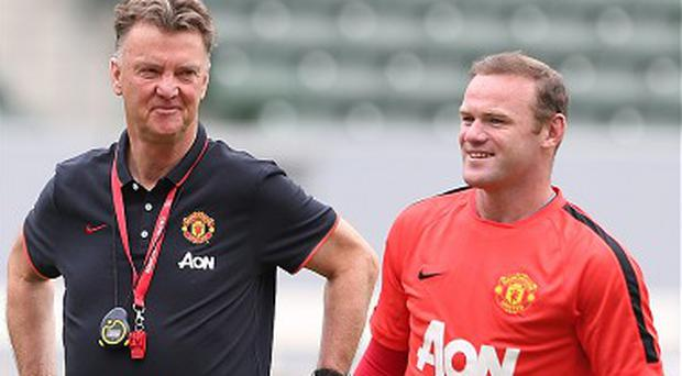 Louis Van Gaal shares a joke with Wayne Rooney during pre-season training