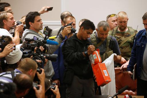 A Malaysian expert (C) examines a black box belonging to Malaysia Airlines flight MH17 during its handover from pro-Russian separatists, in Donetsk