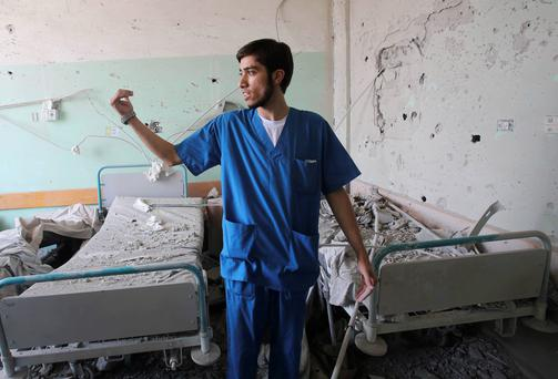 A Palestinian medic gestures at Al-Aqsa hospital, which witnesses said was damaged in an Israeli shelling on Monday, in Deir El-Balah in the central Gaza Strip. Reuters
